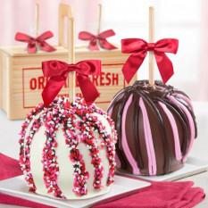 Amo par de maçãs de caramelo com cobertura de chocolate em uma caixa de presente de madeira